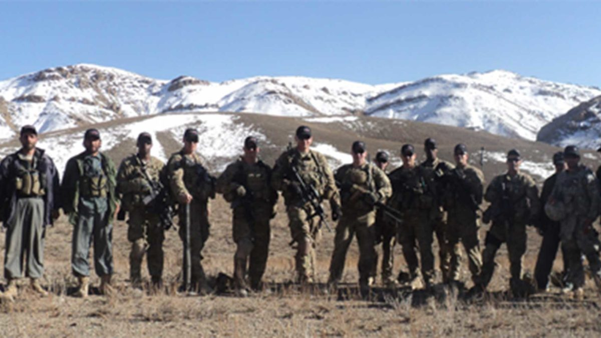 Members of the US Military posing in front of snow capped hills